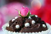 A chocolate muffin decoration with silver balls and a rose bud