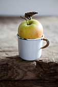 An apple in an enamel cup
