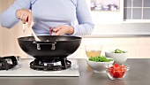 Kartoffeln und Möhren in einen Wok geben