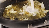Curried onions being quenched with vegetable stock and coconut milk