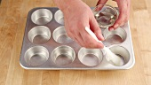 A muffin tin being brushed with oil