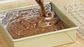 Chocolate fudge mixture being poured into a baking tin lined with aluminium foil