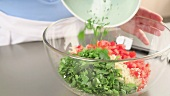 Ingredients for tabbouleh being placed in a bowl