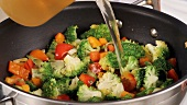 Gemüse in der Pfanne mit Gemüsebrühe ablöschen (Close Up)