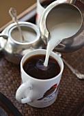 Kaffee mit Milch aufgiessen
