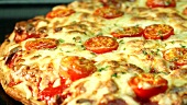 Pizza mit Mozzarella und Kirschtomaten im Ofen backen (Close Up)