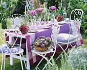 In Lila gedeckter Tisch mit aufgeblühten Artischocken im Freien