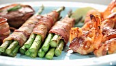 A platter of green asparagus and prawns wrapped in bacon