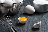 A cracked egg, a whisk and a wire basket of eggs on a stone surface