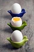 Three boiled eggs in egg cups, one opened