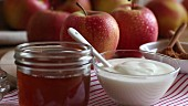 A jar of honey, a bowl of natural yoghurt, cinnamon sticks and apples