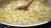 Chicken noodle soup being stirred in a pot (close-up)