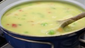 Creamy vegetable soup being stirred (close-up)