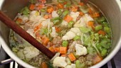 Vegetable soup with meatball being stirred in a pot