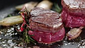Beef fillet with herbs and garlic being fried in a pan