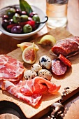 Cutting Board with Prosciutto, Quail Eggs, Figs and Salami; Bowl of Mixed Olives