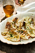 Drizzling Olive Oil Over Grilled Fennel with Fresh Herbs