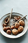 Walnuts and hazelnuts, some cracked, with a nutcracker