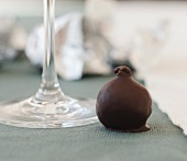 A Chocolate Covered Fig Next to a Wine Glass