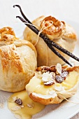 Apple wrapped in pastry with vanilla sauce, raisins and almonds