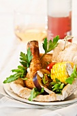 Grilled vegetables and a grilled chicken leg on unleavened bread
