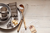 An arrangement of baking tins, a wooden spoon and a whisk