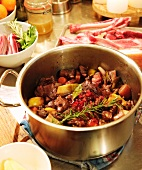 Braised venison ragout in a pot with a sprig of rosemary