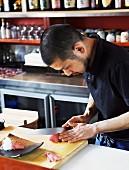 Japanischer Koch mit scharfem Messer, rohes Fischfilet schneidend