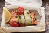 Salmon fillet wrapped in courgette with cocktail tomatoes and lemons on baking paper