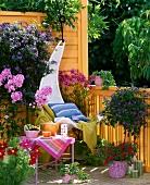 Gemütlicher Hängestuhl auf bunt blühendem Balkon