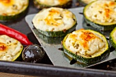Grilled courgette slices with feta cheese on a baking tray