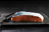 Fresh salmon fillet with skin on a chopping board with a knife