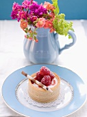 A raspberry tartlet and a bunch of flowers in a jug
