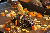 Roast venison with root vegetables in a pan