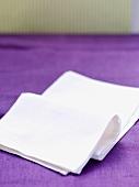 weiße Stoffserviette auf lilafarbener Tischdecke liegend