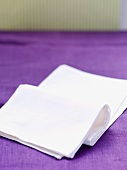 A white napkin on a purple tablecloth