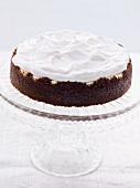 Chocolate cheesecake topped with cream on a cake stand