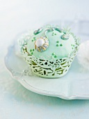 A cupcake with light green icing and decorations