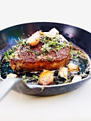 A steak with garlic and thyme