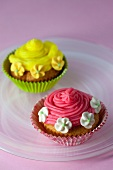 Cupcakes decorated with red and yellow frosting and sugar flowers