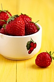 Strawberries in a bowl with a raspberry picture