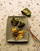 Pineapple wrapped in banana leaves with sesame seeds (Asia)
