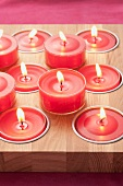 Red tealights on and in wooden board
