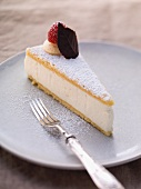 A slice of creamy cheese cake with icing sugar