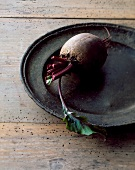A beetroot on an old metal plate