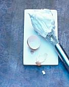 Beaten egg whites on a whisk with eggshells