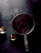 Star anise and cinnamon sticks in an old saucepan