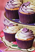 Cupcakes with vanilla and blueberry frosting on a cake stand