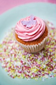 A cupcake decorated with pink frosting and a marzipan butterfly