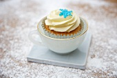 A cupcake decorated with light frosting and a sugar snowflake in a cup